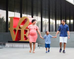 Shara maternity McNay Art Museum waling by the Love sign
